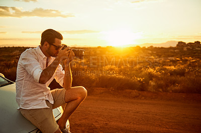 Buy stock photo Shot of a young man taking photos while sitting on the bonnet of a car in a rural landscape