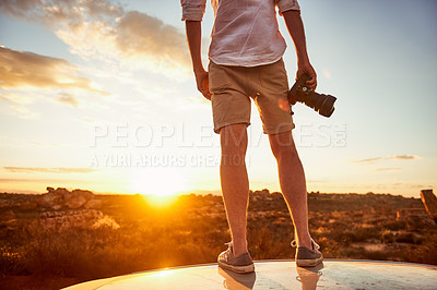 Buy stock photo Rearview shot of a young man holding a camera while standing on top of a car in a rural landscape