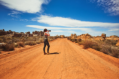 Buy stock photo Shot of a young woman taking photos in a rural landscape