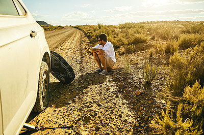 Buy stock photo Shot of a young man sitting on the roadside next to his car with a flat tyre in a rural area