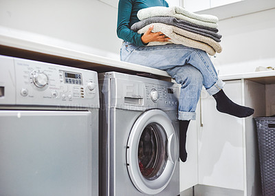 Buy stock photo Closeup shot of an unrecognisable woman holding a stack of towels while sitting on a washing machine at home