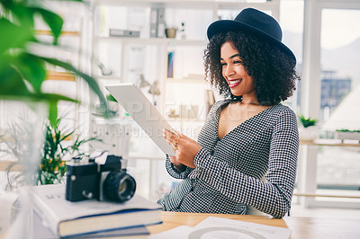 Buy stock photo Cropped shot of a young designer using a digital tablet while sitting at her desk