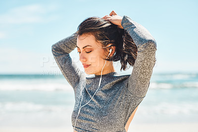 Buy stock photo Shot of a fit young woman tying up her hair during a workout at the beach
