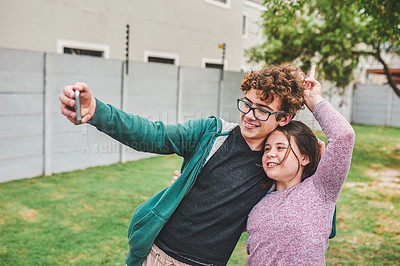 Buy stock photo Shot of a teenage boy taking a selfie with his younger sister in their backyard