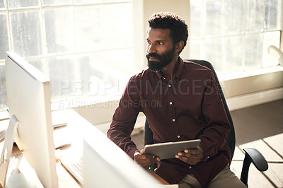 Buy stock photo Shot of a young businessman using a digital tablet while working on a computer in an office