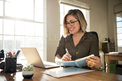 Buy stock photo Shot of a businesswoman making notes while using her laptop
