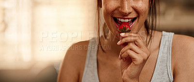 Buy stock photo Cropped shot of a young woman eating a strawberry at home
