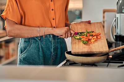 Buy stock photo Cropped shot of a young woman preparing a healthy meal at home