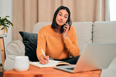 Buy stock photo Shot of a young woman using a smartphone and writing notes while working on the sofa at home