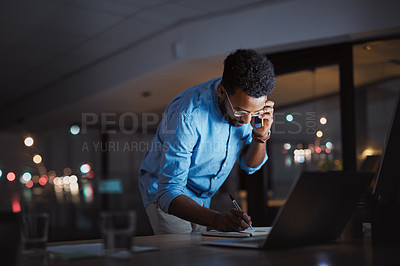Buy stock photo Cropped shot of a handsome young businessman making a phonecall and making notes while working late at night in his office