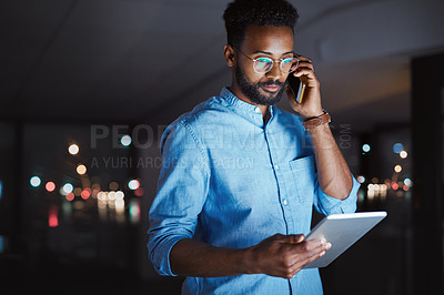 Buy stock photo Cropped shot of a handsome young businessman making a phonecall while working on his tablet late at night in the office