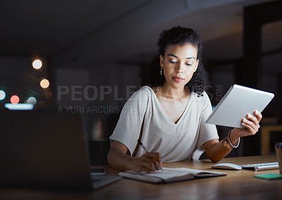 Buy stock photo Cropped shot of an attractive young businesswoman making notes while working on her tablet late at night in the office