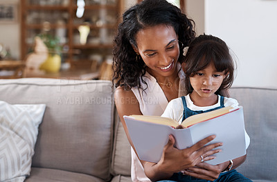 Buy stock photo Shot of a young girl reading a book while sitting with her mother at home