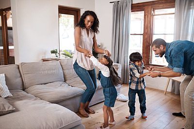 Buy stock photo Shot of a family of four dancing together at home