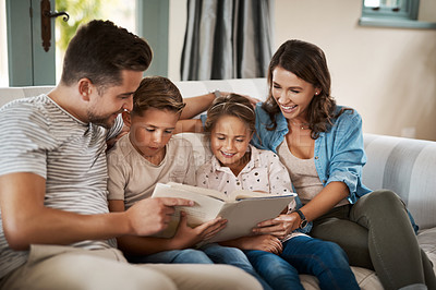 Buy stock photo Shot of a young family of four reading a book together on the sofa at home