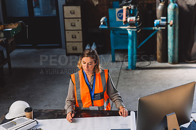 Buy stock photo High angle shot of a female engineer working on blueprints while making use of a computer inside of a workshop