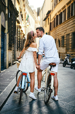 Buy stock photo Shot of a young couple riding bicycles through a foreign city