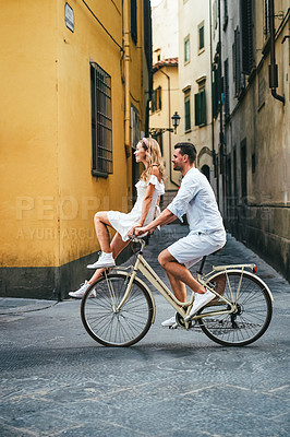 Buy stock photo Shot of a man riding a bicycle with his girlfriend sitting on the handlebar in a foreign city
