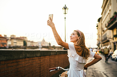 Buy stock photo Shot of a young woman taking a selfie while out cycling in the city