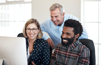 Buy stock photo Cropped shot of a diverse group of businesspeople sitting together and working on a computer in the office