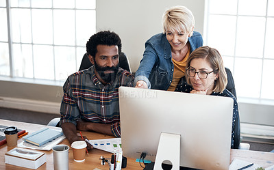 Buy stock photo Cropped shot of a diverse group of creative businesspeople working on a computer together inside their office