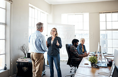 Buy stock photo Cropped shot of two creative businesspeople having a conversation together inside an office with their colleagues working in the background