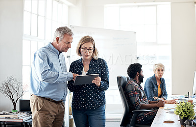 Buy stock photo Cropped shot of two creative businesspeople using a digital tablet together inside an office with their colleagues in the background