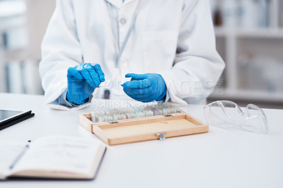Buy stock photo Closeup shot of an unrecognisable scientist working with microscope slides from a box in a lab