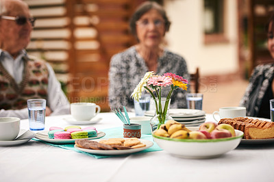 Buy stock photo Cropped shot of an unrecognizable group of elderly people sitting together and enjoying a tea party outdoors
