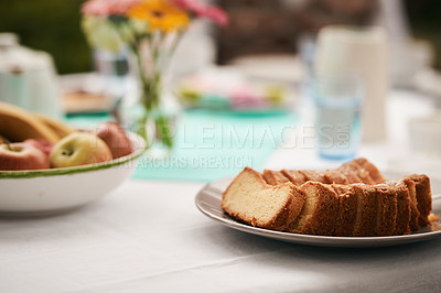Buy stock photo Cropped shot of a sliced vanilla cake and a bowl of fruit on a table for an outdoor tea party