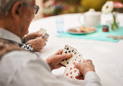 Buy stock photo Cropped shot of an unrecognizable man sitting and holding cards during a game of bridge outdoors