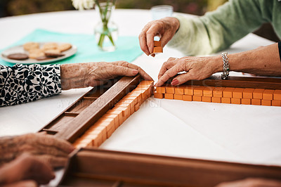 Buy stock photo Cropped shot of an unrecognizable group of seniors sitting and setting up a game of mahjong during a tea party