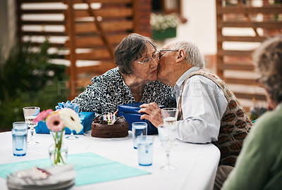 Buy stock photo Cropped shot of a senior man sitting and kissing his wife on the cheek while they celebrate her birthday