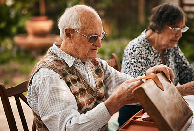 Buy stock photo Cropped shot of a senior man sitting with his friends and setting up a game of mahjong outdoors