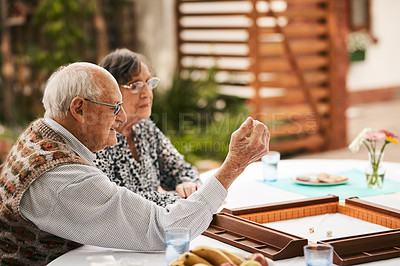 Buy stock photo Cropped shot of a senior man sitting with his friends and playing a game of mahjong outdoors