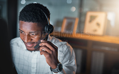 Buy stock photo Cropped shot of a handsome young businessman wearing a headset and sitting alone in his office during a late shift