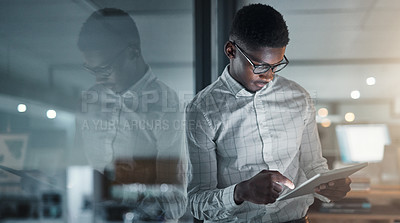 Buy stock photo Cropped shot of a handsome young businessman standing alone in his office and using a tablet during a late shift