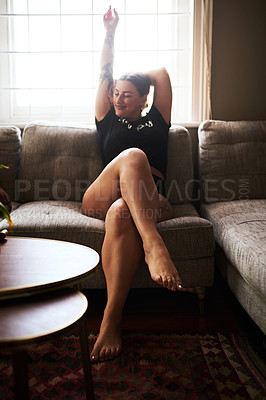 Buy stock photo Full length shot of an attractive young woman sitting on her couch with her arm raised at home