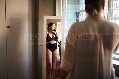 Buy stock photo Cropped shot of an attractive young woman looking thoughtful while standing in front of the mirror in her bedroom at home