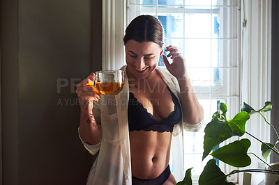 Buy stock photo Cropped shot of an attractive young woman smiling while holding a glass of tea in the morning at home