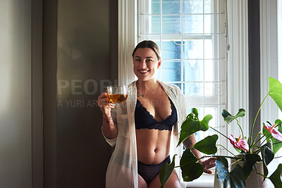 Buy stock photo Cropped portrait of an attractive young woman smiling while holding a glass of tea in the morning at home