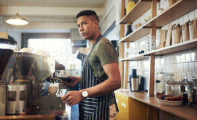 Buy stock photo Shot of a young man operating a coffee machine in a cafe