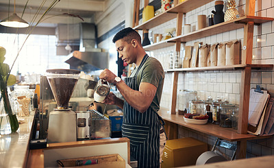 Buy stock photo Shot of a young man preparing a cup of coffee in a cafe