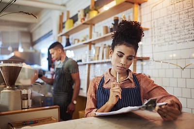Buy stock photo Shot of a young woman going through notes on a clipboard while working in a cafe