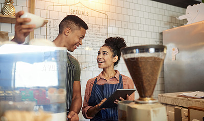 Buy stock photo Shot of a young man and woman using a digital tablet while working together in a cafe