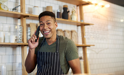 Buy stock photo Shot of a young man talking on a phone while working in a cafe