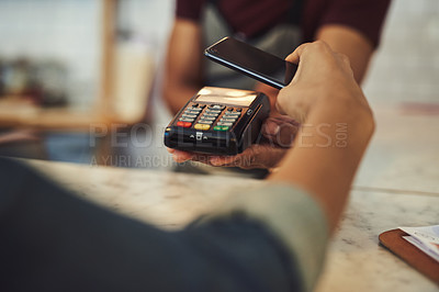 Buy stock photo Closeup shot of a customer making a payment with a cellphone in a cafe