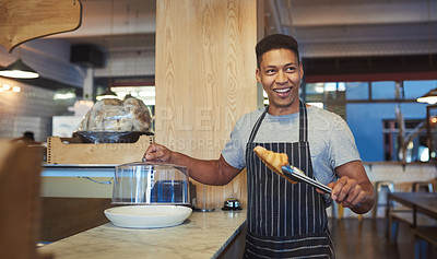 Buy stock photo Shot of a young man holding a croissant with tongs in a cafe