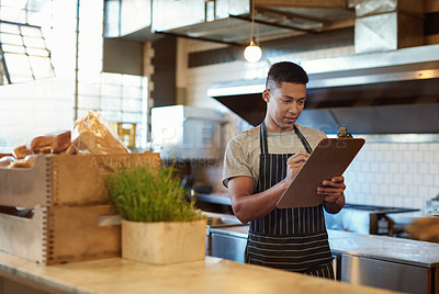 Buy stock photo Shot of a young man using a clipboard while checking stock in a cafe