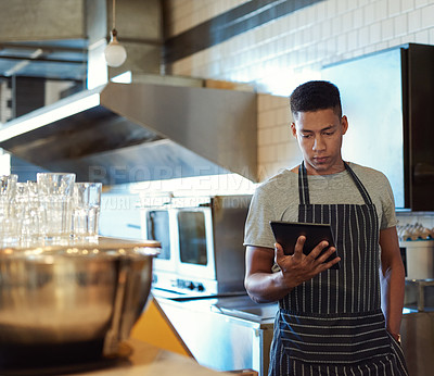 Buy stock photo Shot of a young man using a digital tablet while working in a cafe